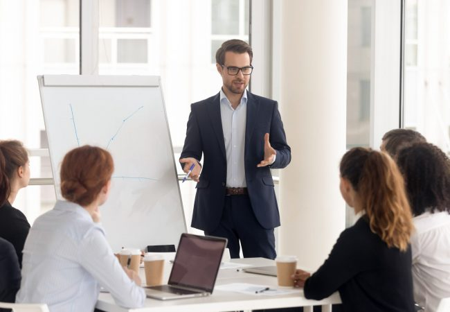 Male business coach speaker in suit give flipchart presentation, speaker presenter consulting training persuading employees client group, mentor leader explain graph strategy at team meeting workshop